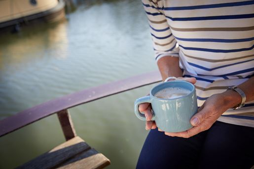 The torso of a woman who is holding a mug of tea or hot chocolate on a boat on the canal.