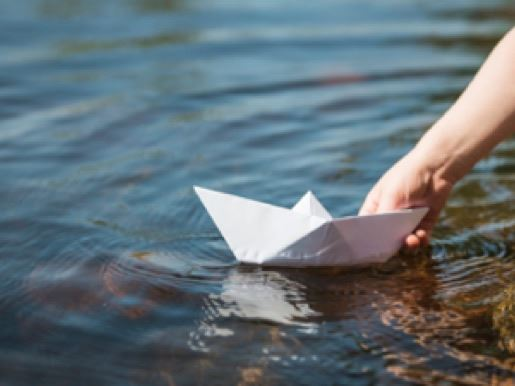An origami paper boat on the water