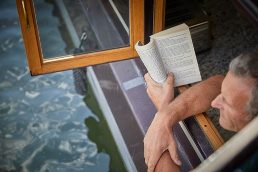 A man reading a book at the window of a canal boat.