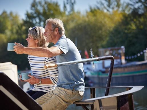 A man and a woman having a cup of tea on top of a canal boat