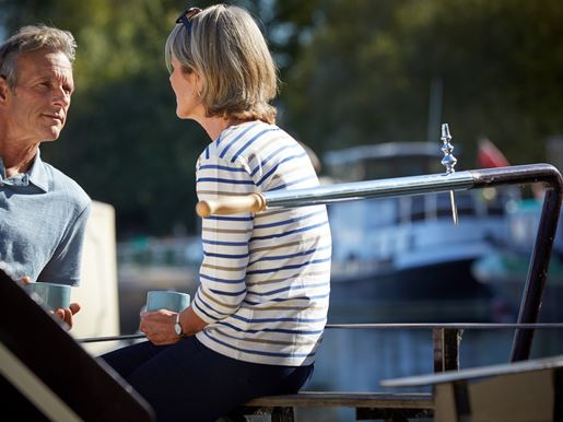 Man and woman share a hot drink on a boat